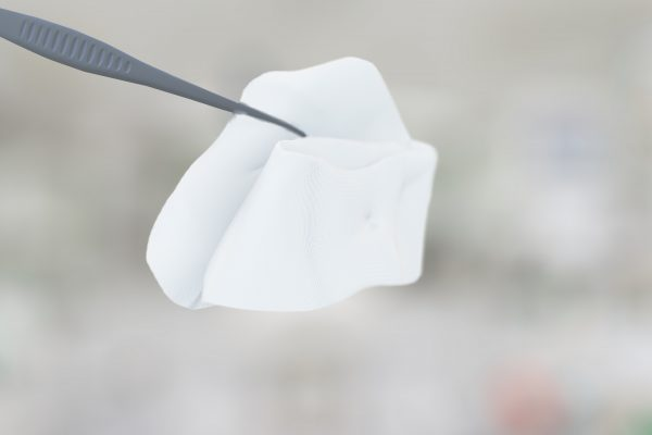 Tweezers hold a compress on a blurred background.